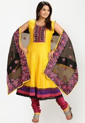 embroidered suit set for women from Salwar Studio. Made from Chanderi silk, it comprises a kameez, churidar and dupatta. The flared, sleeveless kameez features an asymmetric neckline, regular fit and knee length. The exquisitely designed yoke contributes to the gorgeous look of this suit set from Salwar Studio. The yellow coloured kameez with colourful detailing on the hemline adds a creative touch to its look. The dupatta further adds oodles of charm to this suit set from Salwar Studio.