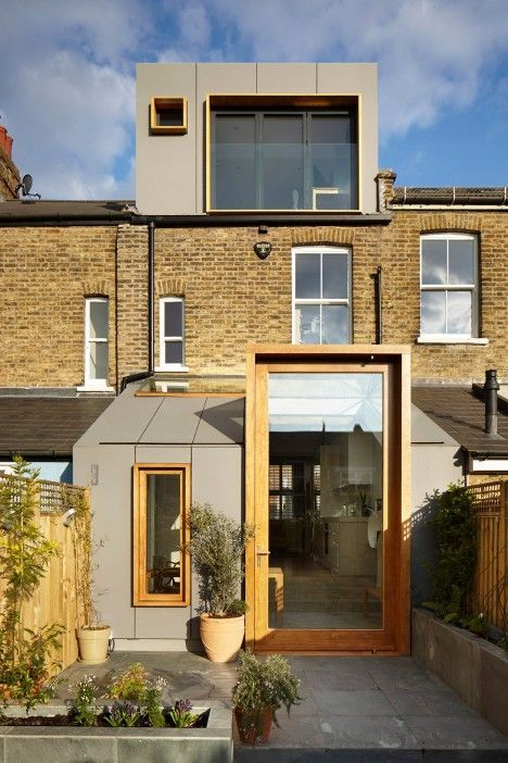A three-metre-high pivoting glass door protrudes from the sloping roof of this London house extension, which is clad in fibre-cement panels to match a refurbished dormer window (+ slideshow). Designe
