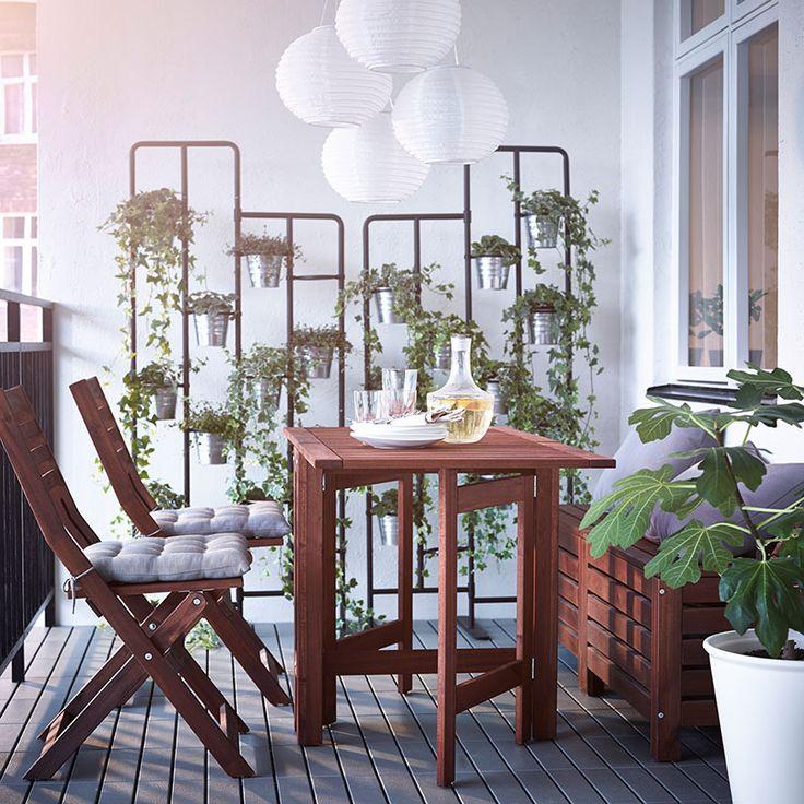 Balcone con sedie pieghevoli, tavolo a ribalta e panche in legno marroni, e piedistalli grigi con piante