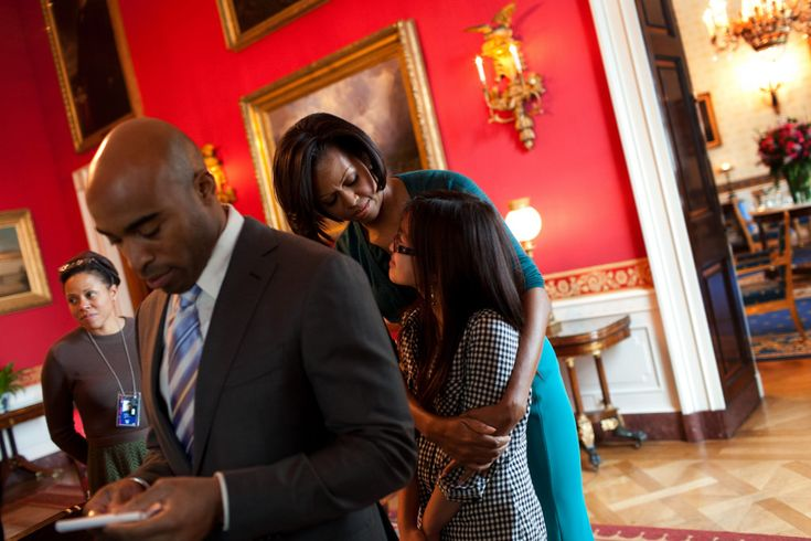First Lady Michelle Obama hugs student Tammy Nguyen in the Red Room of the White House before an event announcing a campaign to combat the rapidly growing problem of childhood obesity while Tiki Barber checks his notes before they take the stage, Feb. 9, 2010. (Official White House Photo by Samantha Appleton)  This official White House photograph is being made available only for publication by news organizations and/or for personal use printing by the subject(s) of the photograph. The ph...