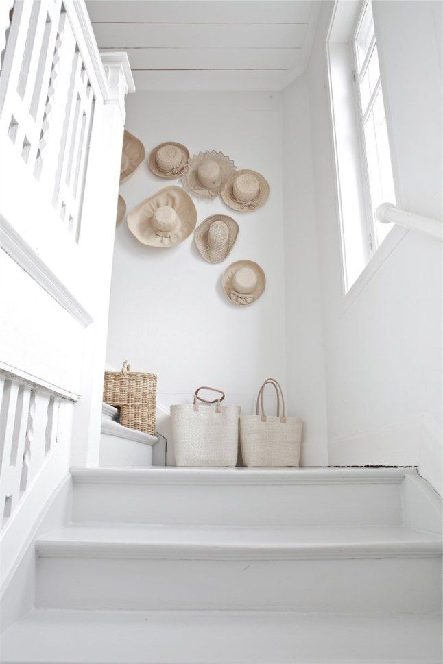Beautiful creamy white staircase - fun hat decoration on the wall! #staircase #white #interiordesign