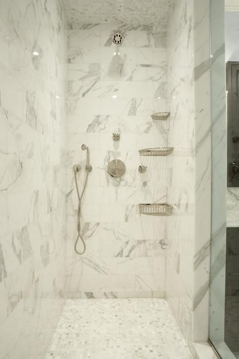 Stunning walk-in shower with seamless glass door and gray and white marble tiled interior with white marble mosaic tiled floors and ceiling over dual shower heads alongside corner mount shelves.