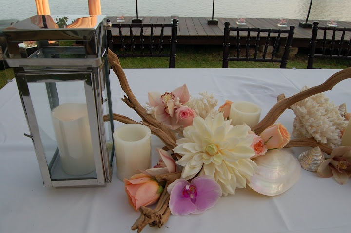 Coral, driftwood, silver lanterns along with Dahlia's, pink cymbidium orchids and peach and pink garden roses make up an elegant dining table centerpiece.