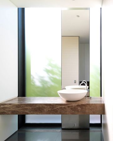 wood slab vanity | with full height mirror leaned on floor to ceiling glass window