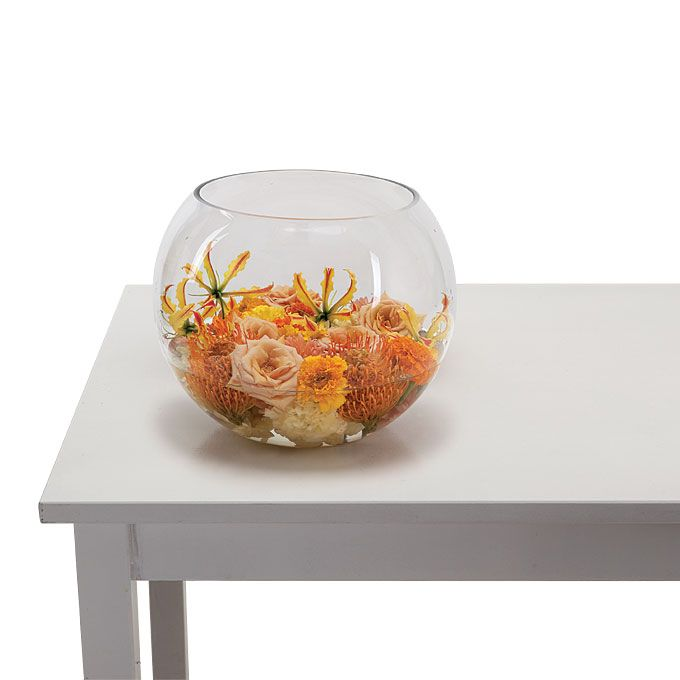 """Brides.com: Centerpieces You Can Actually Afford. Bright, monochromatic colors always elevate the look of inexpensive blooms (like carnations and marigolds). Arrange them in a """"bath"""" for some modern drama—and enough savings to allow you to include a few pricier blooms (like nerines and proteas), too.  Carnations, marigolds, dahlias, Sahara roses, gloriosa lilies, and proteas  in a fishbowl, QuatreCoeur."""