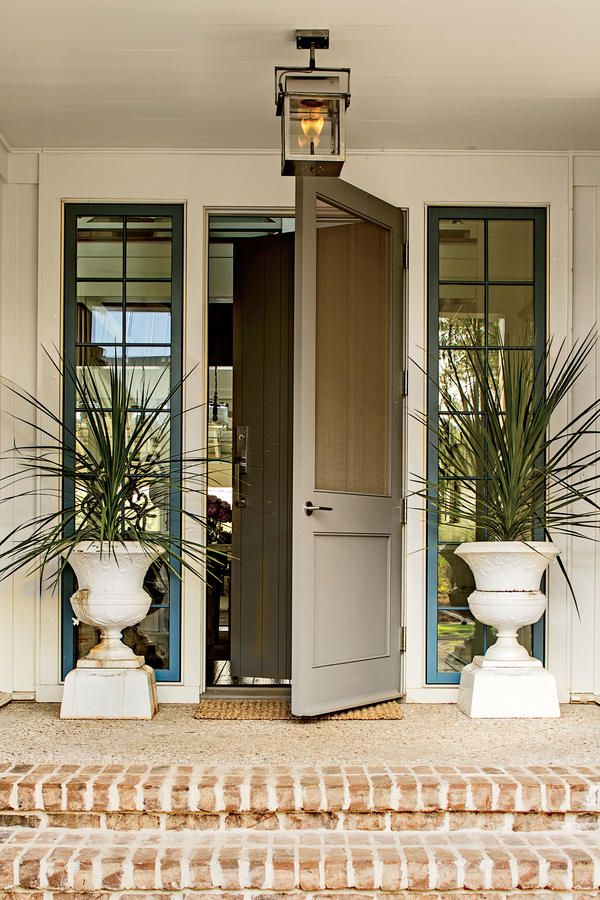 Ken hung a classic screened door over the front door to lessen the entry's formality and set a relaxing tone. Gas lanterns in a stainless steel finish from Bevolo (bevolo.com)complementthe house's coolcolor palette.