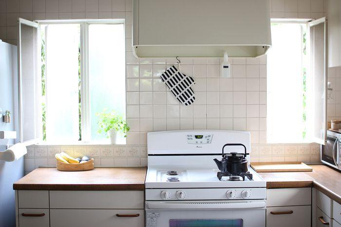 シンプル&ミニマルな暮らしぶりが支持を集めている人気ブログ『うらうらな日々。』。運営者・みしぇるさん宅のキッチンは窓が多く、風が通り抜けるとても明るい空間です。    ヴィンテージ感漂うアメリカ製の白いホーローのガスコンロと、ナチュラルなウッドのキッチンカウンターが味わいのある佇まい。築30年という年月を経て、あちこち修理が必要な箇所もあるそうですが「古さにもすっかり愛着がわきました」とお気に入りのようです。