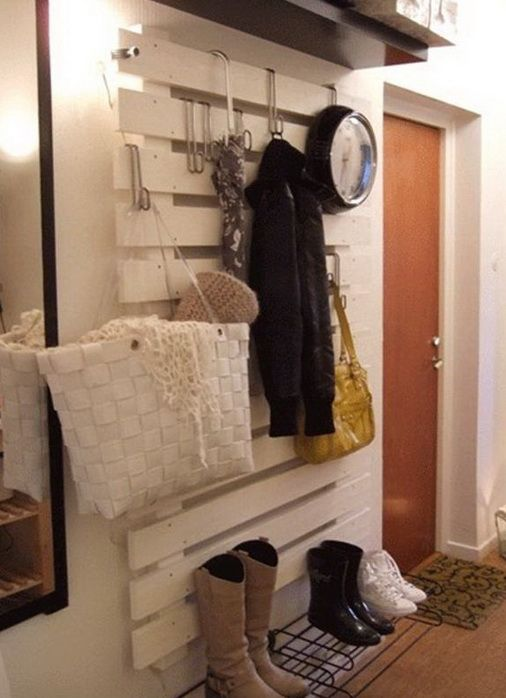 A full wall clothes and shoes organizing hanging area made from a pallet painted white