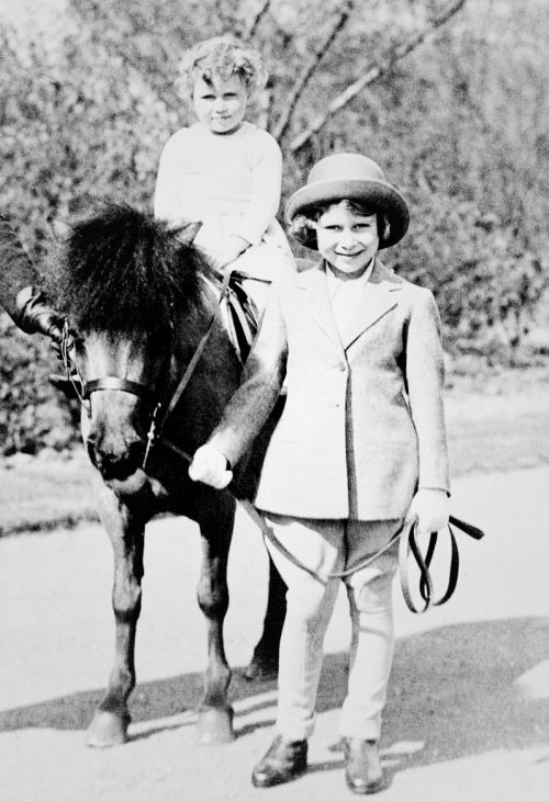 "Photograph of Princess Elizabeth (b. 1926), later Queen Elizabeth II, with Princess Margaret (1930-2002). Princess Margaret is sitting on ""Peggy"", a Shetland pony, while Princess Elizabeth is holding the reins, 1934."