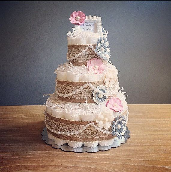 This listing is for a three tier pink and grey rustic shabby chic diaper cake with pearl and flower accents and is topped with a personalized