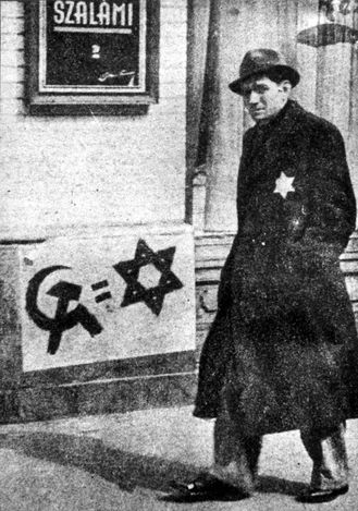 Budapest, Hungary, 1944, A Jewish man in the street, beside a propaganda placard where Jews are compared to communists.