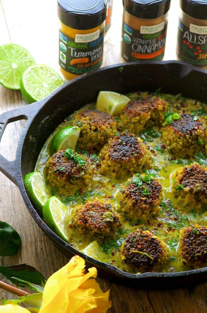 Cauliflower Quinoa Meatless Meatballs in Coconut Turmeric Broth in a cast iron pan with slices of lime and some spice bottles in the background