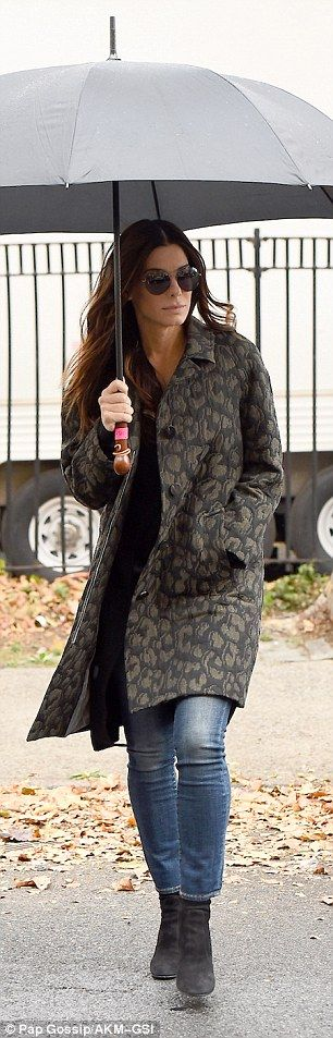 The brunette beauty looked as if she meant business as she held onto her wide black umbrella with a wood handle