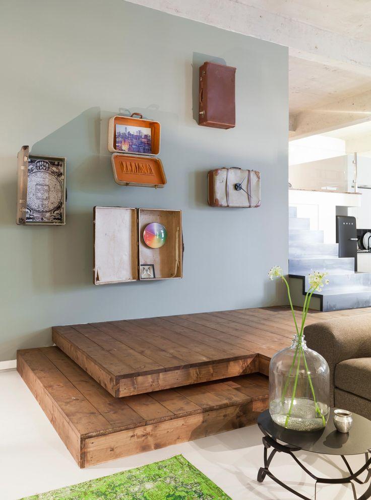 Een gave wand is hier gemaakt met oude koffers, de muur is geverfd in de kleur Parallel.