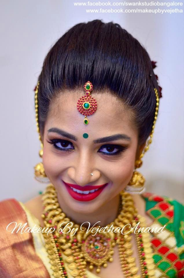 Traditional Southern Indian bride, Dr. Suganya wears bridal silk saree and jewellery for her Muhuratam. Makeup and hairstyle by Vejetha for Swank Studio. Red lips. Bridal gold jewellery. Silk sari. Maang tikka. Tamil bride. Telugu bride. Kannada bride. Hindu bride. Malayalee bride. Bridal Saree Blouse Design. Indian Bridal Makeup. Indian Bride. Gold Temple Jewellery. Statement Blouse. Find us at https://www.facebook.com/SwankStudioBangalore