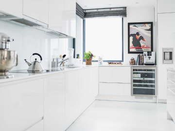 Puhtaanvalkoinen kerrostaloasunnon keittiö, jossa hauskoja yksityiskohtia ja ylellinen viinikaappi. #etuovisisusus #keittiö #puustelli