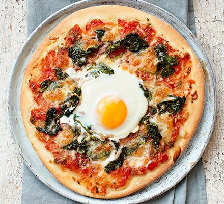 Follow our easy recipe to make your own pizza dough, top with spinach and mozzarella and finish with an egg cracked in the centre