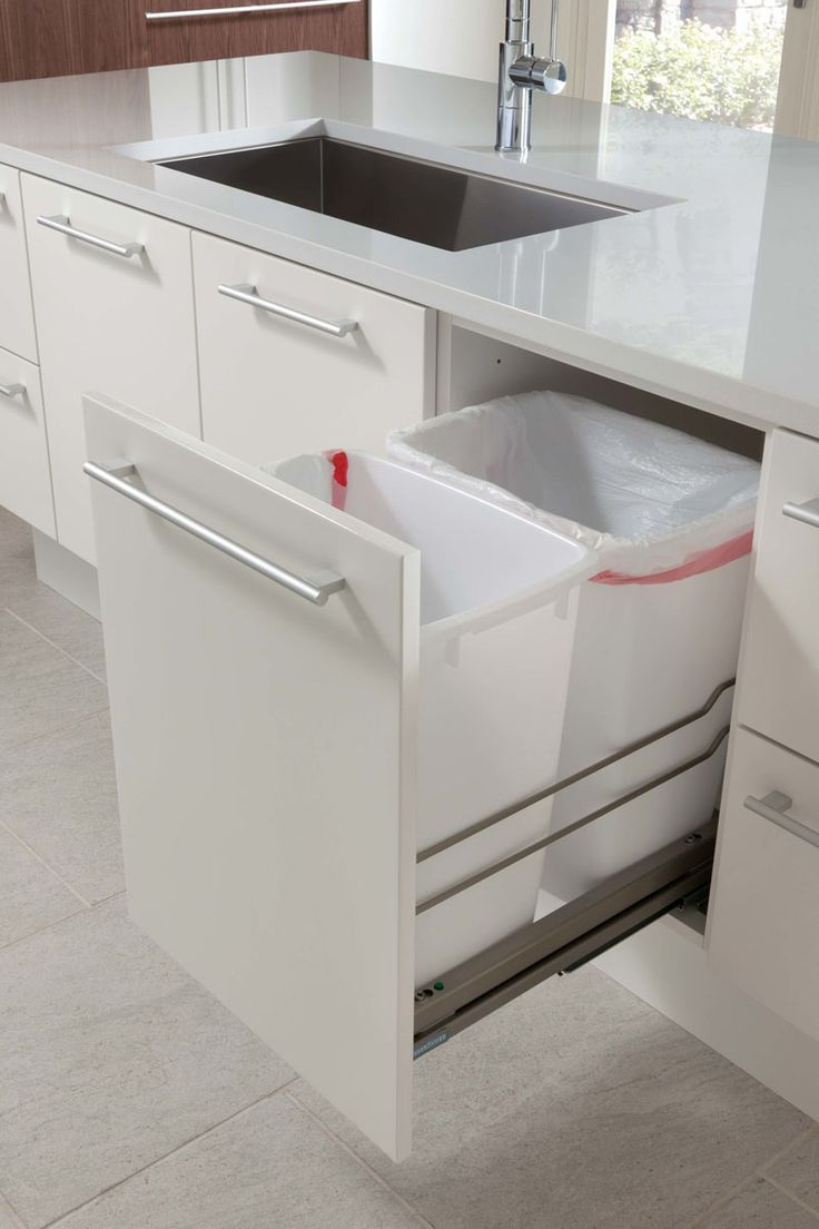 Kitchen Design Idea - Hide Pull Out Trash Bins In Your Cabinetry | These trash bins sit on the pull out shelf next to the sink where much of the food prep is done, making it easy to wipe food remnants off the counter and into the bin.