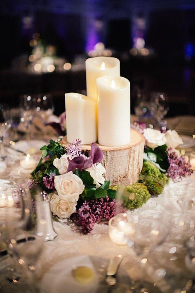 rustic wedding centerpieces three white candles on a wooden log surrounded by roses and lilacs eli turner studios