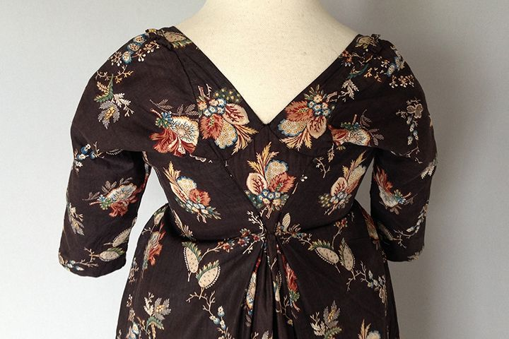 French Ramoneur Short Gown, 1790s. Dark brown cotton ground hand block printed with four large sprays 3 in / 8 cm of flowers and leaves, in shades of rust, ochre, blue, green and black. Round gathered neck with woven ties, the fabric caught into pleats to give shape to the bust opening to reveal two flaps which secure to the centre, brass hooks and eyes, an addiitonal piece of chequered tape with a brass eye high waist, elbow length sleeves, the back with a V neck edged with a frill at the…