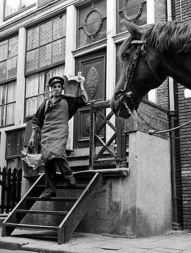 Riolering vroeger. Een stronttonnetjesschepper met twee emmers vol uitwerpselen uit een huis in de Jordaan in Amsterdam op weg naar de boldootkar van de gemeentereiniging. 13 september 1953.Faeces-collector collecting toilet-waste in buckets. Amsterdam, the Netherlands, 1953.