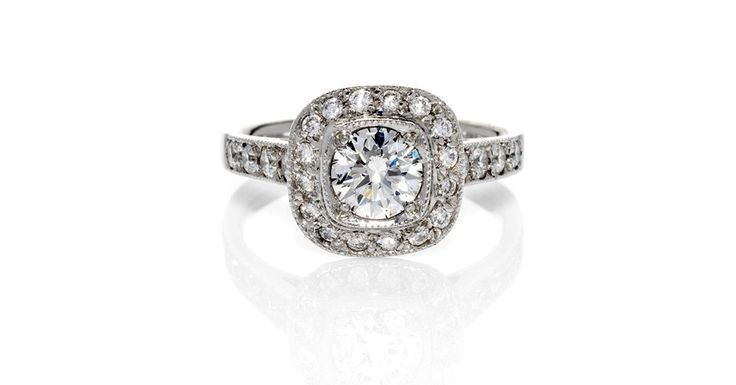 Aura. Art Deco Inspired Diamond Ring Design with Round Brilliant Cut Central Diamond in Cushion Shape Setting with Grain Set Diamond Halo and Shoulders and Milgrain Detail.