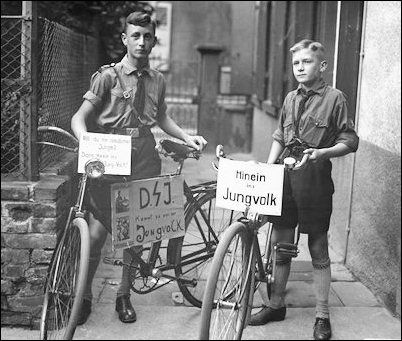 "Hitler Youths on bicycles with publicity signs saying ""Are you a German boy?"" and ""Come into our Jungvolk!"""