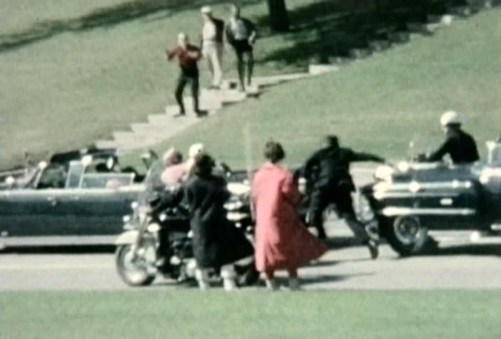 Motorcade onlooker Marie Muchmore captures Mary Ann Moorman (in Blue) about to snap her famous Polaroid picture as her friend Jean Hill (in Red) looks on. Secret Service Agent Clint Hill has begun his run to the Presidential Limoisine in an attempt to protect President Kennedy and the First Lady.  This is a frame from Muchmore's 8mm home movie.