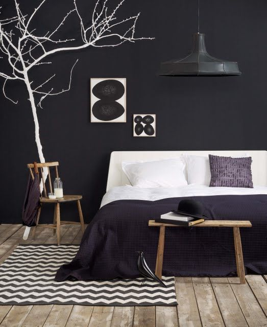 Amazing black bedroom with white tree limb.Love the pops of white.