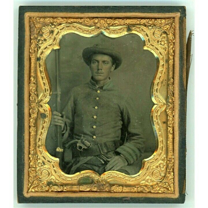 """Incredible 6th Plate Tintype of Private Kenneth A. (""""K.A."""") McIntosh, Company K, 6th Tennessee Infantry, C.S.A.  Nineteen-year old Kenneth lived on a farm outside Brownsville, Tennessee when the War came.  He Enlisted in Captain John Ingram's Company, which became K of the 6th Tennessee, a unit that was purportedly well-drilled and, if McIntosh's portrait is indicative, also smartly uniformed:  he sports a gray frock coat with pale blue cuff and collar facings, and is armed in addition to…"""