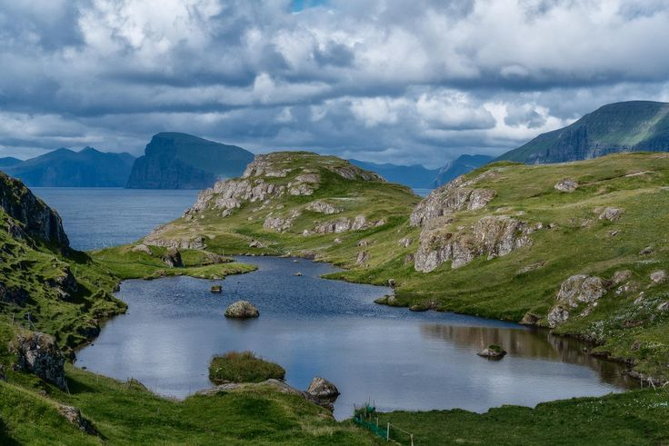 Green rocky terrain and blue waters, underneath a stormy sky, provide an incredibly beautiful outlook near the town of Skopun on the island of Sandoy in the Faroe Islands.
