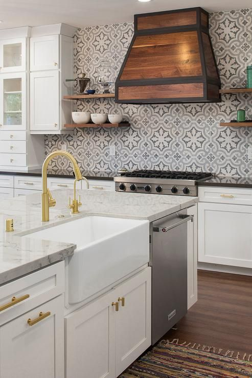 A white island is fitted with a KitchenAid dishwasher and a farmhouse sink with a gold gooseneck faucet fixed to a marble countertop above white shaker cabinets adorning brass knobs.