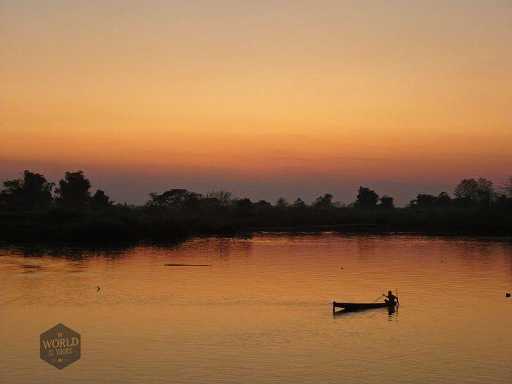 Als de rode bal achter de heuvels is verdwenen, keert de man zijn boot. Luang Prabang maakt zich op voor de nacht.