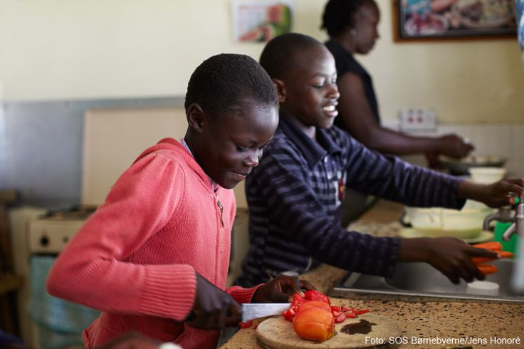 Et par børn fra SOS-børnebyen i Eldoret i Kenya hjælper deres SOS-mor i køkkenet.