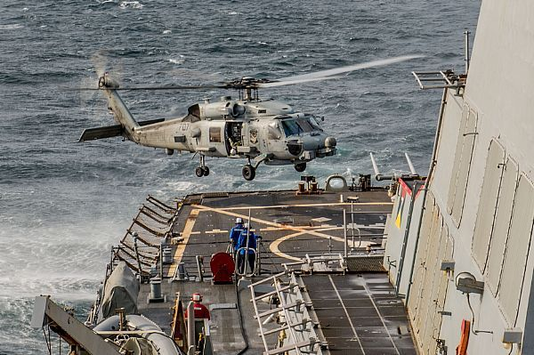 "An MH-60R Sea Hawk helicopter, from the ""Saberhawks"" of Helicopter Maritime Strike Squadron (HSM) 77, lands on the flight deck of the forward-deployed Arleigh Burke-class guided-missile destroyer USS Barry (DDG 52) during exercise Invincible Spirit."