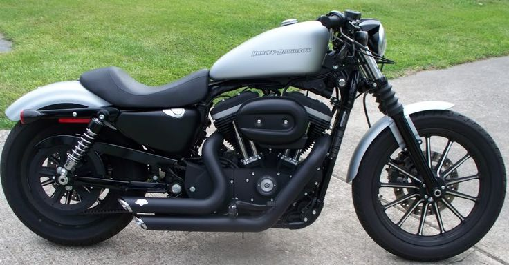 Sportster Iron 883 with drag bars, Vance and Hines pipes, and a relocated speedo.