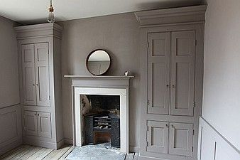 Wardrobes created in alcoves with fireplace surround
