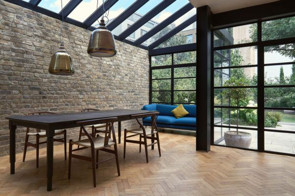 Contemporary dining area with cool pendant lights, brick wall and Crittal windows