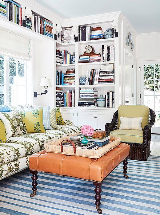 """The cozy family room is a study in pattern and texture. """"I love the mix of upholstery fabrics with the leather ottoman and wicker chairs,"""" says Mark. """"The bookshelves balance the kitchen cabinets across the room."""" The rug is antique, and the tray is Ralph Lauren Home."""