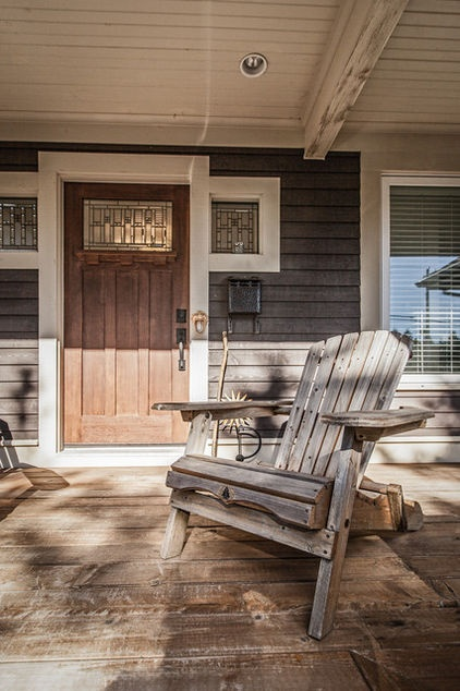 """From Houzz, """"A large front veranda, dark brown wood clapboard and cedar shake siding, and large eave overhangs add to the charm of this Craftsman-style home. The color of the front door with stained glass windows plays off the cedar shakes."""""""