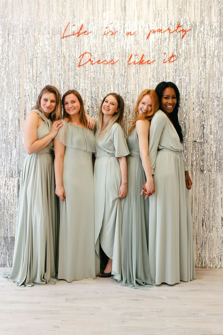 Sage green mix & match bridesmaid dresses against a glittery silver backdrop | Different styles of dress in the same colour by twobirds Bridesmaid featuring L-R the Classic Ballgown, Maya dress, Lucy dress, Tulle ballgown & the Margaux dress