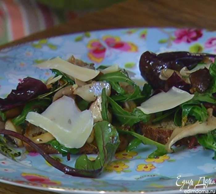 На обжаренный хлеб выложить грибы с салатом, посыпать хлопьями сыра.