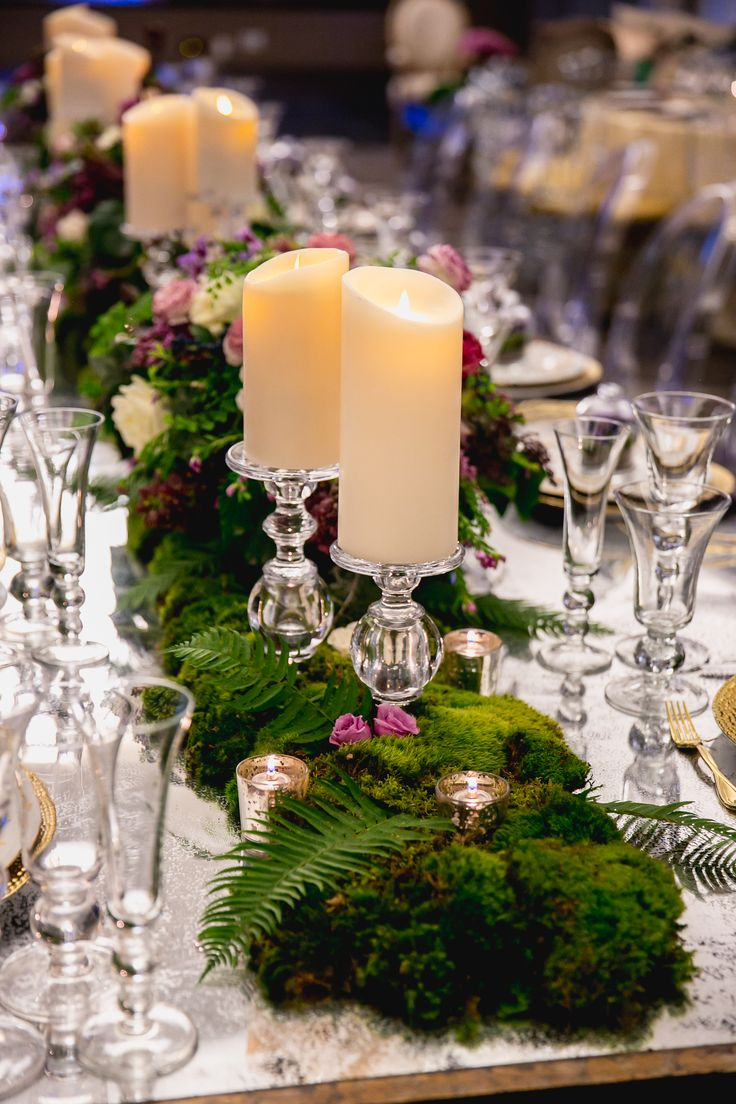 A Combination Of Fern And Moss Speckled With Purple Blooms Draped Down The  Middle Of Long Dining Tables. White Candles Perched On Top Of Glass Stands  Added ...