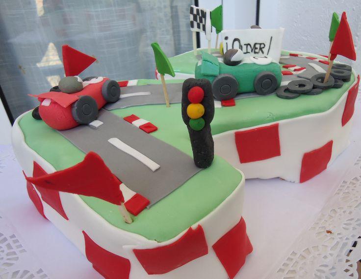 Tarta moldeada con el numero dos con temática de carrera de coches, con tres coches de carreras, carretera y meta.