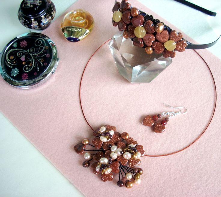 """Set: Diademă, cercei şi colier """"Pulbere de stele"""" din colecţia de piatra soarelui (goldstone) """"Flori de piatră Bijoux"""" Didina Sava. Colierul este confecţionat din inimioare de goldstone, mărgele de granat, perle de cultură aurii şi ivoire, mărgele de jasp, mărgele de nisip, bănuţi de agat, sârmă modelatoare argintată neoxidabilă şi neagră, pe un suport de oţel siliconat.  De vânzare"""