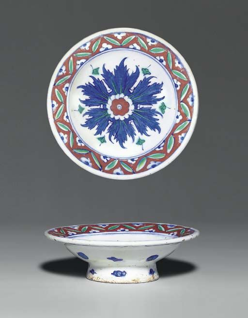 AN IZNIK POTTERY TAZZA  OTTOMAN TURKEY, CIRCA 1580  With sloping rim and of shallow form on high foot, the white interior painted with large central stylized blue flowerhead with red and green highlights, the rim with repeated paired green leaves over red ground with white and blue half-flowerheads, the exterior with alternating blue roundels and trefoils,   7¼in. (18.6cm.) diam.