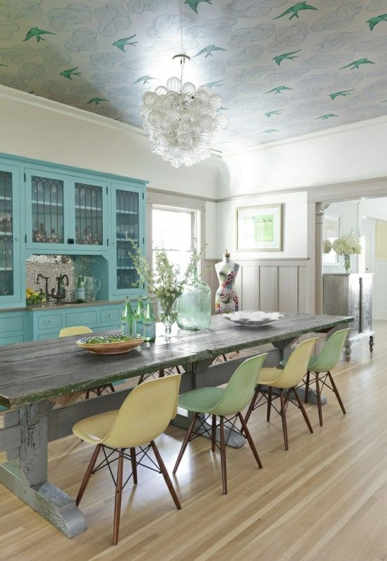 A kitchen made whimsical by coordinating turquoise birds that bring the eye upward and tie together the rest of the decor. Get the look with Cole & Son wallpaper Tropical Birds in Bleu.