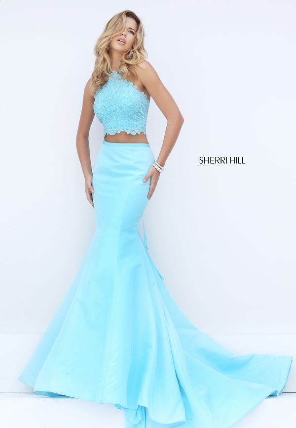 Trip the light fantastic in the sensational Sherri Hill 50419 two-piece prom dress. This irresistible ensemble pairs a crop top with a sleek trumpet skirt. The halter top is styled in lace and showcases a scalloped edged midriff and semi-open back. A slim ribbon band adorns the waistline, tying in long streamers at the back. The long trumpet skirt flares smoothly and showcases a ruffled inset sweep train.