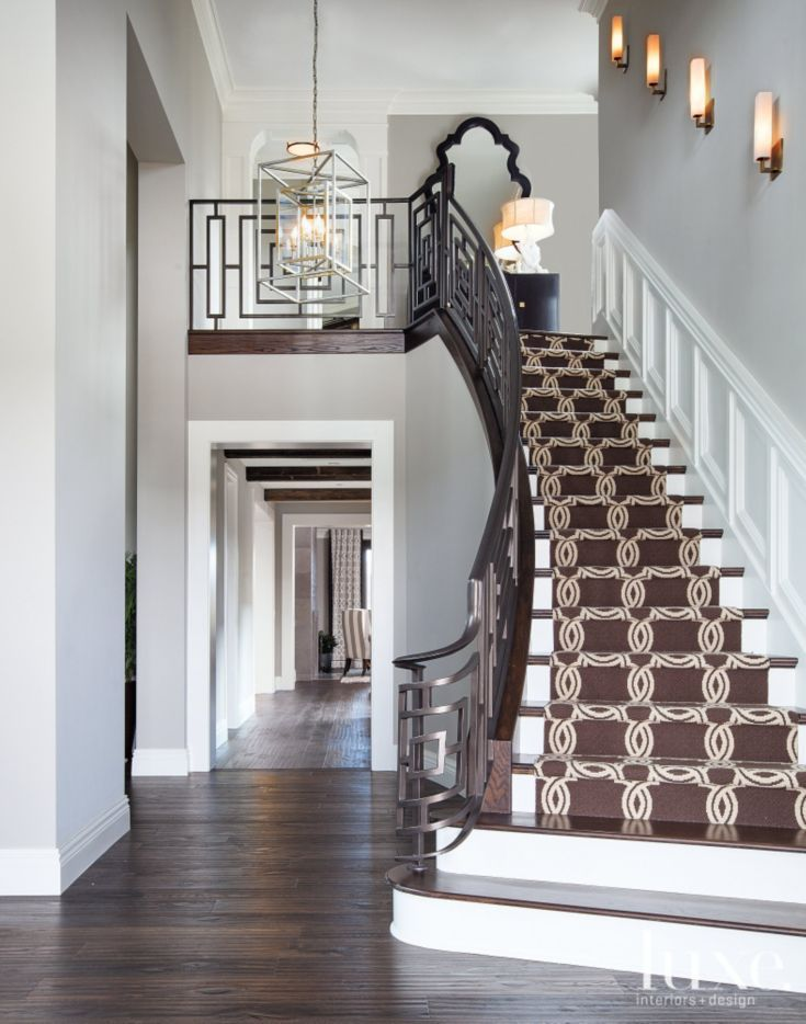 Designer Rebecca Robeson added hand-forged ironwork pieces throughout this house, including a geometric railing for the entry staircase. A stair runner by Crescent Carpet Importers lends additional graphic punch.