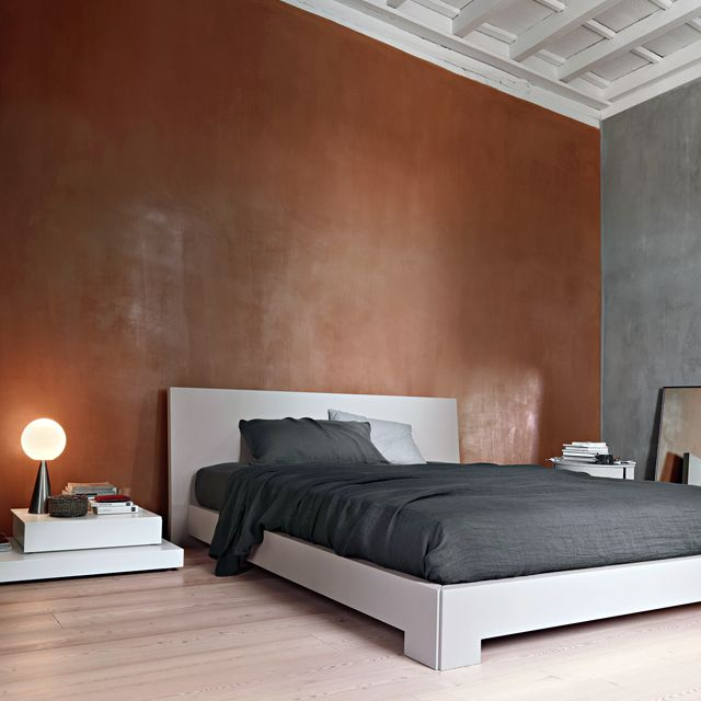 grey bed in apartment with high ceiling